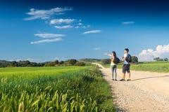 Pares jovenes felices en el campo en primavera Imagenes de archivo