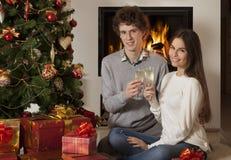 Pares jovenes felices en interior de la Navidad Imagen de archivo