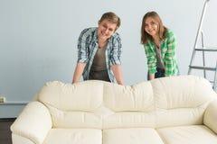 Pares jovenes felices en interior de planificación de la camisa del vaquero detrás del sofá blanco fotos de archivo libres de regalías