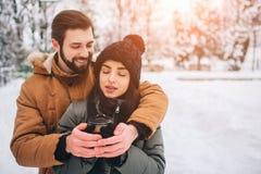 Pares jovenes felices en invierno Familia al aire libre hombre y mujer que parecen ascendentes y risa Amor, diversión, estación y Fotos de archivo libres de regalías
