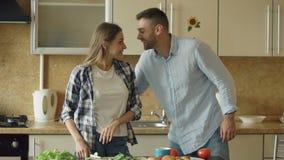 Pares jovenes felices en la cocina La mujer atractiva que cocina el desayuno y abofetea a su novio que quiera probar la comida almacen de video