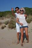 Pares jovenes felices en la playa Imagenes de archivo