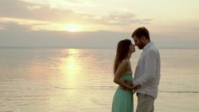 Pares jovenes felices en la playa en la puesta del sol Miran en uno a ojos del ` s almacen de metraje de vídeo