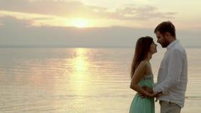 Pares jovenes felices en la playa en la puesta del sol Miran en uno a ojos del ` s metrajes