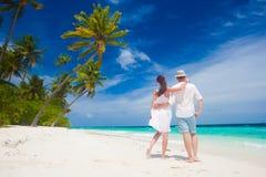 Pares jovenes felices en la ropa blanca que camina por la playa maldives Imágenes de archivo libres de regalías
