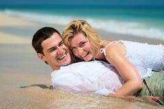 Pares jovenes felices en las arenas tropicales Foto de archivo