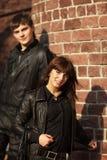 Pares jovenes felices en las chaquetas de cuero en la pared Fotos de archivo libres de regalías