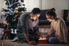Pares jovenes felices en los sombreros de santa que se sientan con los regalos de Navidad en piso fotos de archivo