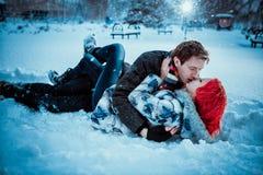 Pares jovenes felices en parque del invierno Fotografía de archivo