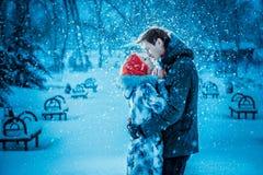 Pares jovenes felices en parque del invierno Imagenes de archivo