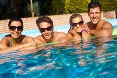 Pares jovenes felices en piscina foto de archivo
