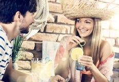 Pares jovenes felices en restaurante de la playa en el verano Imagenes de archivo