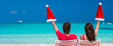 Pares jovenes felices en Santa Hats roja que se sienta encendido Foto de archivo libre de regalías