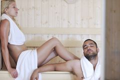 Pares jovenes felices en sauna fotos de archivo