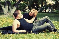 Pares jovenes felices en un parque Foto de archivo libre de regalías