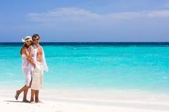 Pares jovenes felices en una playa Imagen de archivo libre de regalías