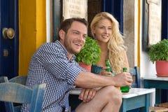 Pares jovenes felices en vacaciones de verano en el restaurante al aire libre. Fotos de archivo libres de regalías