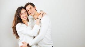 Pares jovenes felices que abrazan en un fondo blanco Imagenes de archivo