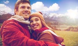 Pares jovenes felices que abrazan sobre las montañas de las montañas Imágenes de archivo libres de regalías