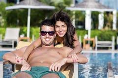 Pares jovenes felices que abrazan y que se relajan en la piscina Fotos de archivo libres de regalías