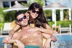 Pares jovenes felices que abrazan y que se relajan en la piscina Fotografía de archivo libre de regalías