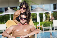 Pares jovenes felices que abrazan y que se relajan en la piscina Imagenes de archivo
