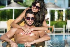 Pares jovenes felices que abrazan y que se relajan en la piscina Foto de archivo