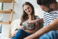 pares jovenes felices que acarician el gato en casa mientras que se sienta fotos de archivo libres de regalías