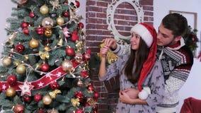 Pares jovenes felices que adornan el árbol de navidad en suéteres lindos y sombreros del rojo de santa almacen de video