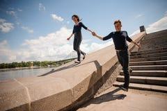 Pares jovenes felices que celebran las manos y el funcionamiento abajo de las escaleras Imagen de archivo