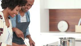 Pares jovenes felices que cocinan junto almacen de metraje de vídeo