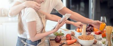 Pares jovenes felices que cocinan junto en la cocina en casa Mirada de la tableta imagen de archivo libre de regalías