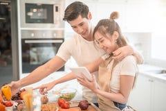 Pares jovenes felices que cocinan junto en la cocina en casa Mirada de la tableta Foto de archivo libre de regalías