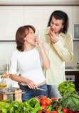 Pares jovenes felices que cocinan verduras en cocina Foto de archivo libre de regalías