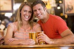 Pares jovenes felices que comen cervezas en una barra Imágenes de archivo libres de regalías