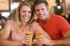Pares jovenes felices que comen cervezas en una barra Foto de archivo