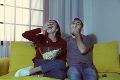 Pares jovenes felices que comen las palomitas mientras que ve la TV fotos de archivo