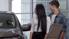 Pares jovenes felices que compran el nuevo automóvil en la representación, leyendo el papel de información metrajes