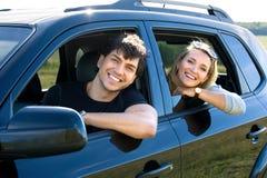 Pares jovenes felices que conducen el coche Fotos de archivo
