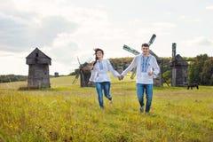 Pares jovenes felices que corren en el campo Fotos de archivo