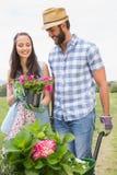 Pares jovenes felices que cultivan un huerto junto Fotos de archivo