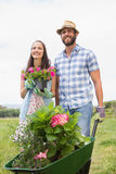 Pares jovenes felices que cultivan un huerto junto Fotografía de archivo
