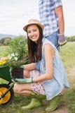Pares jovenes felices que cultivan un huerto junto Foto de archivo