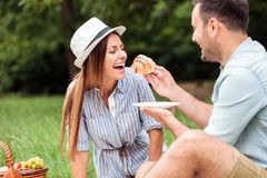 Pares jovenes felices que desayunan relajante en parque, comiendo los cruasanes y bebiendo el café imagen de archivo