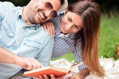 Pares jovenes felices que disfrutan de día en naturaleza, leyendo un libro y mintiendo en una manta de la comida campestre fotografía de archivo libre de regalías