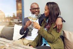 Pares jovenes felices que disfrutan de una bebida romántica Imagen de archivo libre de regalías