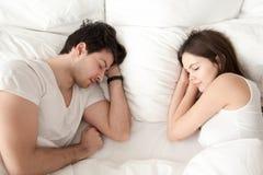 Pares jovenes felices que duermen junto en la cama, gozando de drea dulce Imagen de archivo libre de regalías