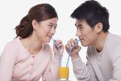 Pares jovenes felices que enlazan y que comparten un vidrio de zumo de naranja, tiro del estudio Fotografía de archivo