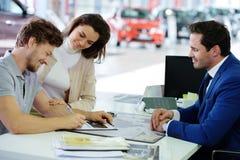 Pares jovenes felices que firman un contrato para comprar un nuevo coche en la sala de exposición de la representación Fotos de archivo libres de regalías