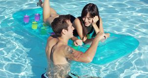 Pares jovenes felices que flotan en el colchón en piscina almacen de metraje de vídeo